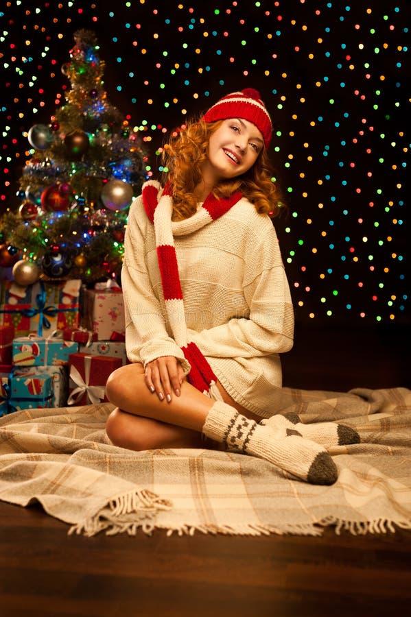 Junge lächelnde Frau, die nahe Weihnachtsbaum sitzt stockfoto