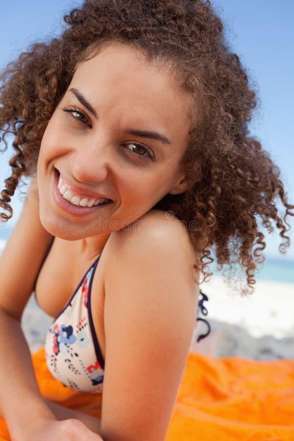 Junge lächelnde Frau, die sich auf einem Badetuch beim Anstarren entlang hinlegt stockbilder
