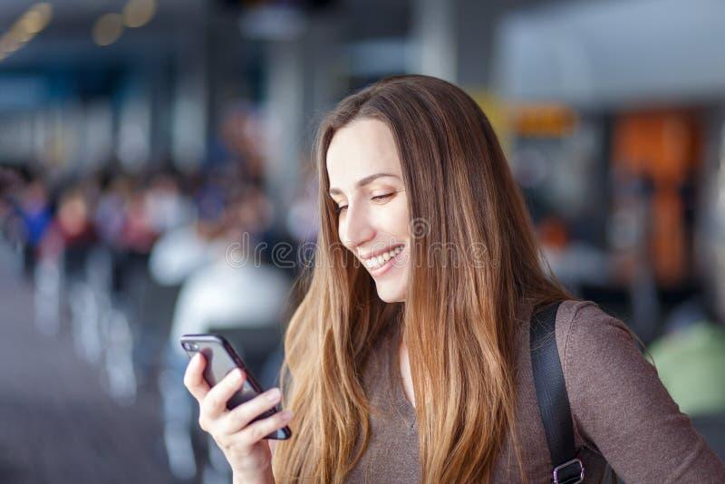 Junge lächelnde Frau, die Smartphone im Flughafen verwendet stockbild