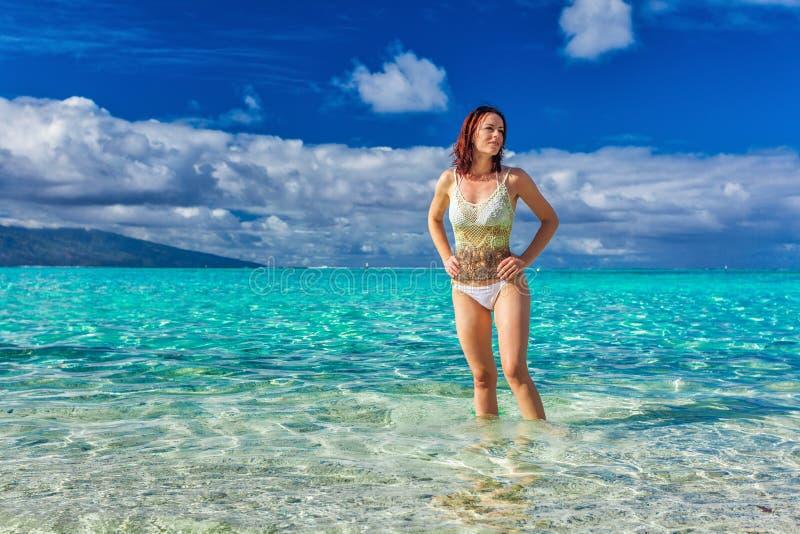 Junge lächelnde Frau, die Spaß auf dem tropischen Strand hat lizenzfreie stockfotos