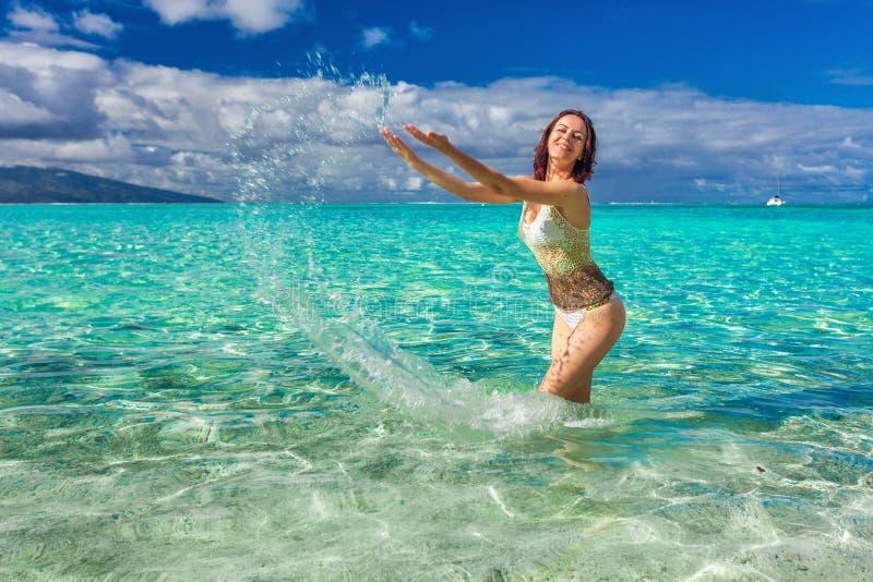 Junge lächelnde Frau, die Spaß auf dem tropischen Strand hat lizenzfreies stockfoto