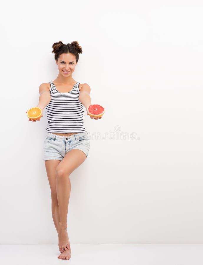 Junge lächelnde Frau, die Zitrusfrucht hält Porträt im vollen Wachstum nahe der weißen Wand stockbilder
