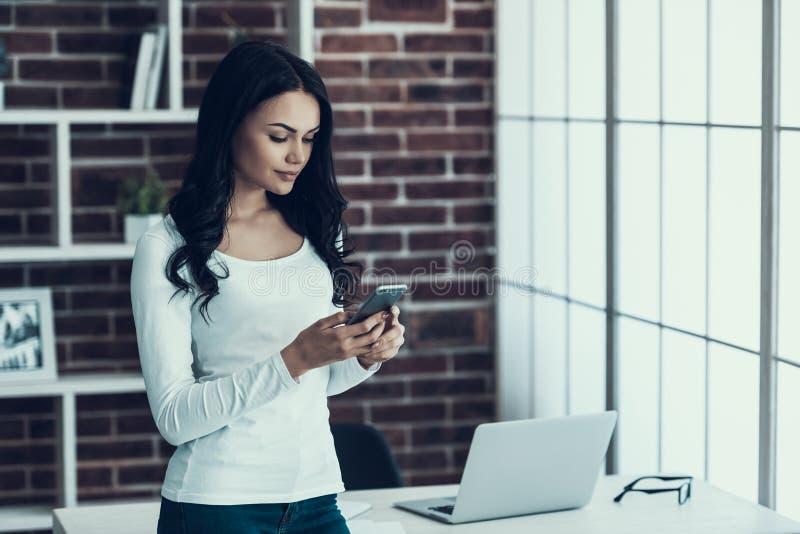 Junge lächelnde Frau, die zu Hause Smartphone verwendet stockbilder