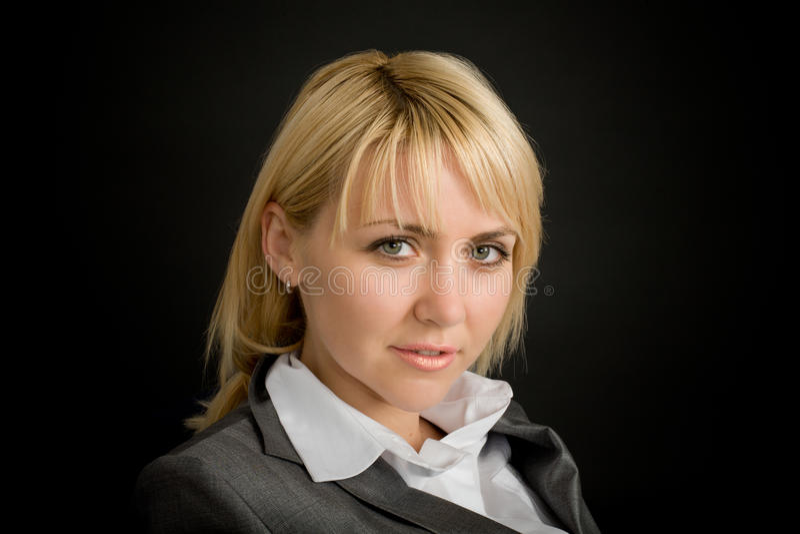 Junge lächelnde Frau in einem Anzug stockfotografie