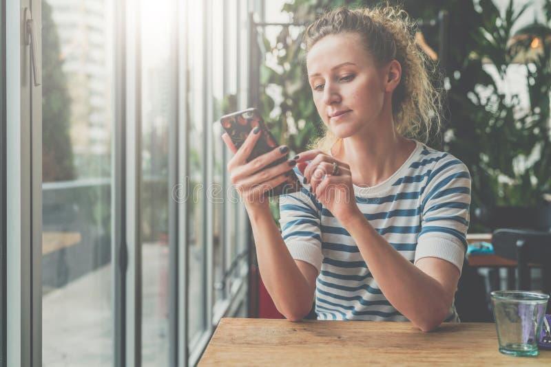 Junge lächelnde Frau in gestreifter Bluse sitzt im Café am Holztisch nahe Fenster und benutzt den Smartphone und liest eBook stockfotos