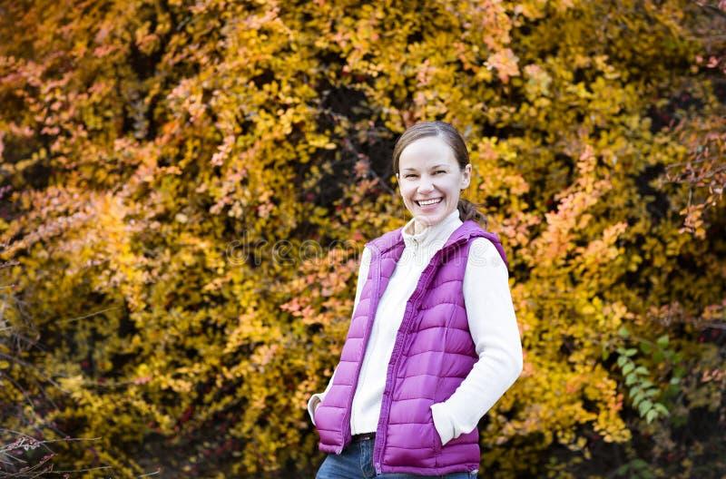 Junge lächelnde Frau im Herbstwald stockfotos