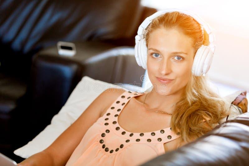 Junge lächelnde Frau mit den Kopfhörern, die auf dem Sofa online hörend Musik unter Verwendung eines Smartphone sich entspannen stockbild
