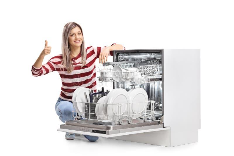 Junge lächelnde Frau mit einer offenen vollen Spülmaschine, die Daumen aufgibt stockbild