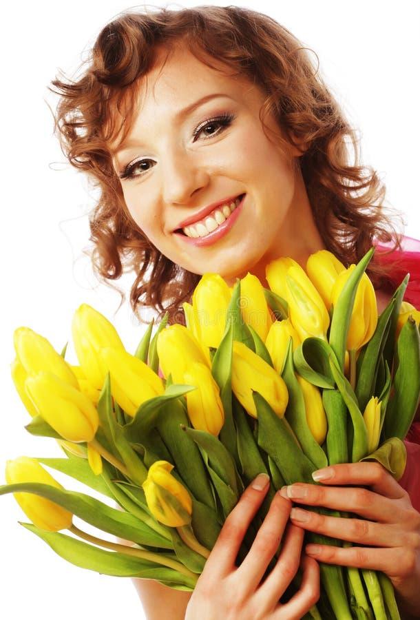 Junge lächelnde Frau mit gelben Tulpen stockbilder