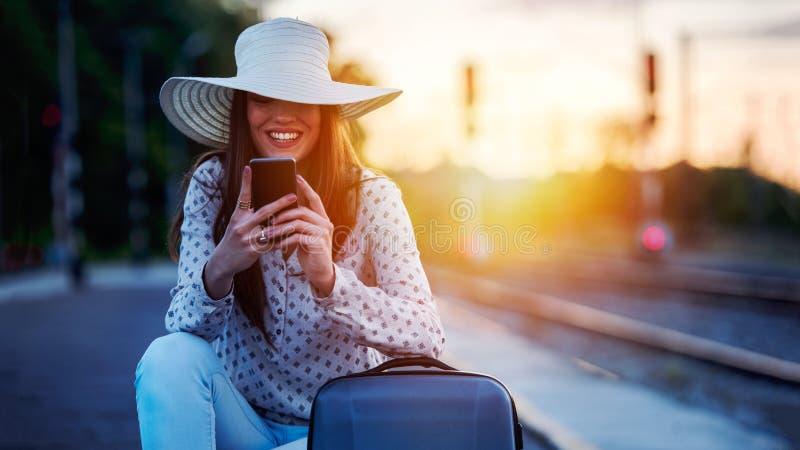 Junge lächelnde Frau mit Gepäck auf Bahnstation unter Verwendung des intelligenten Telefons lizenzfreie stockbilder