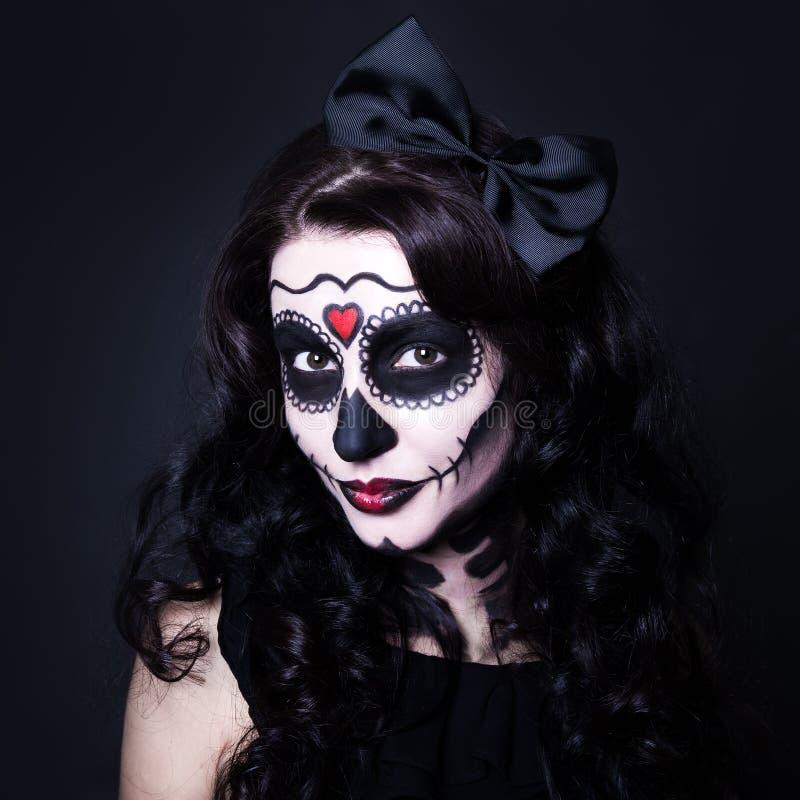 Junge lächelnde Frau mit Halloween-Schädel bilden über Schwarzem lizenzfreies stockfoto