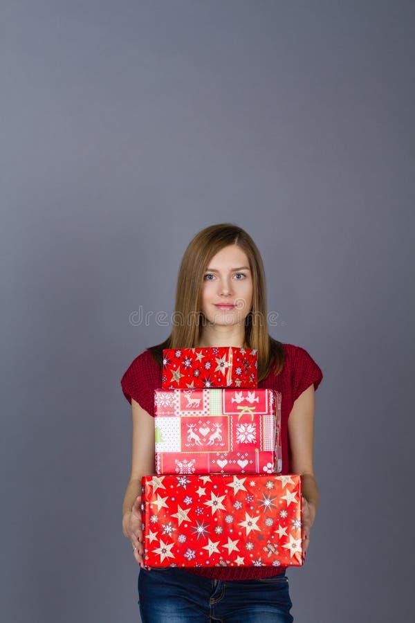 Junge lächelnde Frau mit Weihnachtsgeschenken lizenzfreie stockbilder