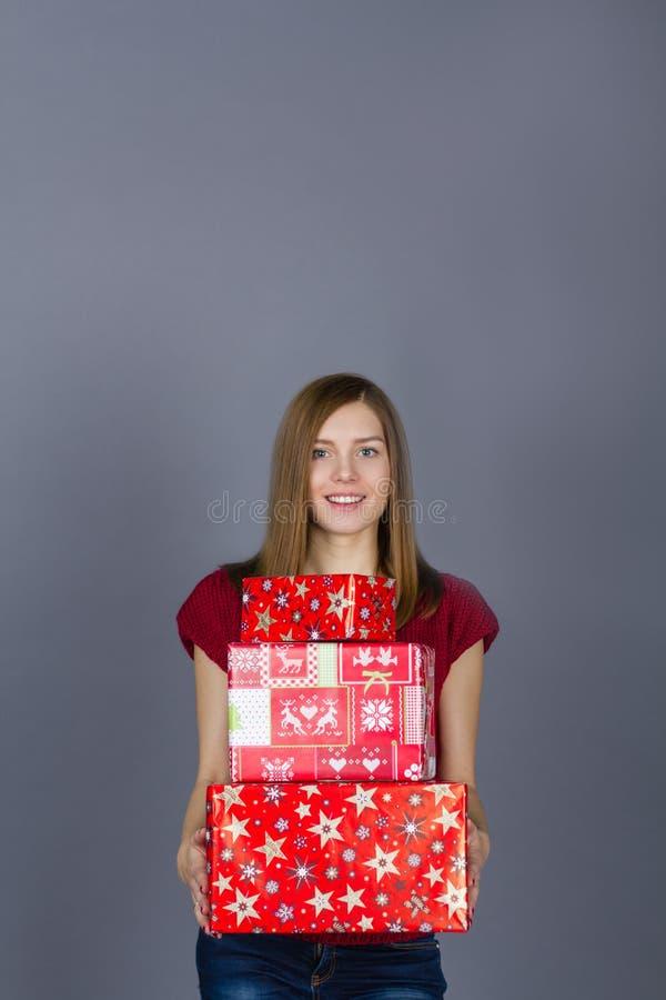 Junge lächelnde Frau mit Weihnachtsgeschenken lizenzfreies stockbild