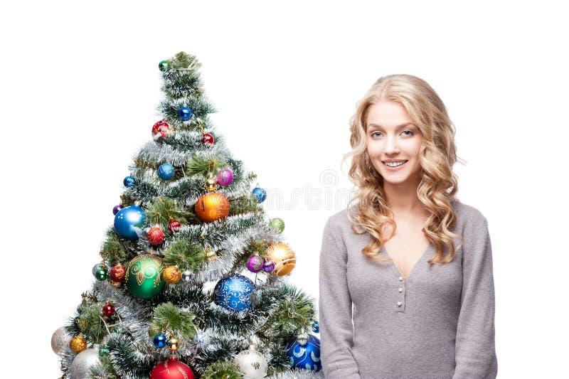Junge lächelnde Frau nahe Weihnachtsbaum stockbild