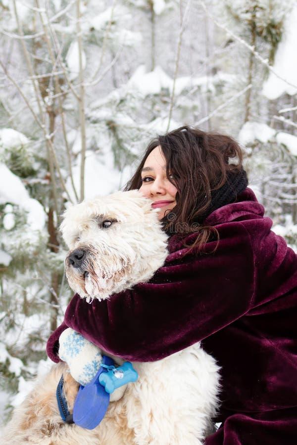 Junge lächelnde Frau umarmt ihren russischen Südschäfer Dog auf einem Hintergrund des Winterkoniferenwaldes stockfotografie