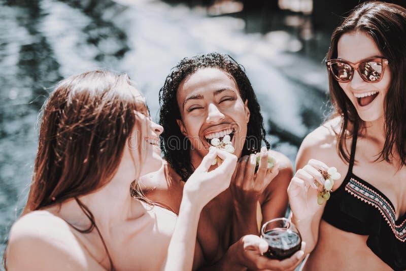 Junge lächelnde Frauen, die Wein am Poolside trinken lizenzfreie stockbilder
