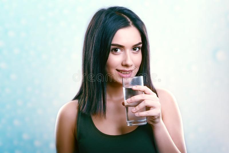Junge lächelnde Frauenholding und Trinkwasserglas lizenzfreies stockbild