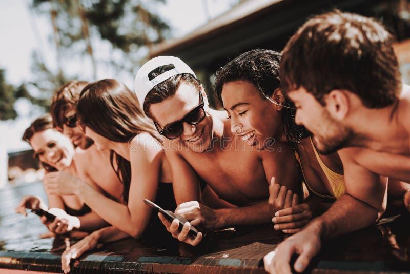 Junge lächelnde Freunde, die Smartphone am Poolside verwenden lizenzfreie stockfotos