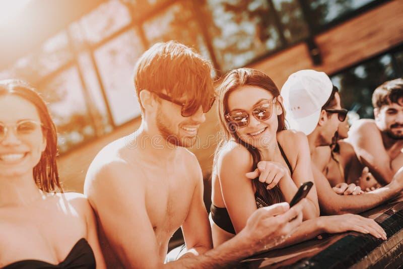 Junge lächelnde Freunde, die Smartphone am Poolside verwenden stockbilder