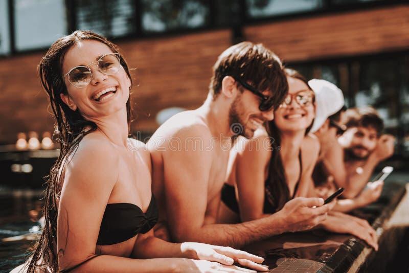 Junge lächelnde Freunde, die Smartphone am Poolside verwenden lizenzfreie stockbilder