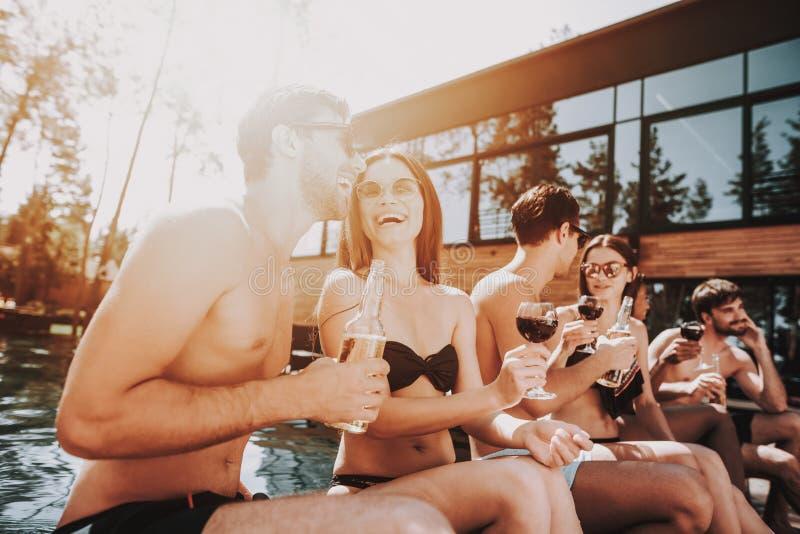 Junge lächelnde Freunde, die Wein am Poolside trinken lizenzfreie stockbilder