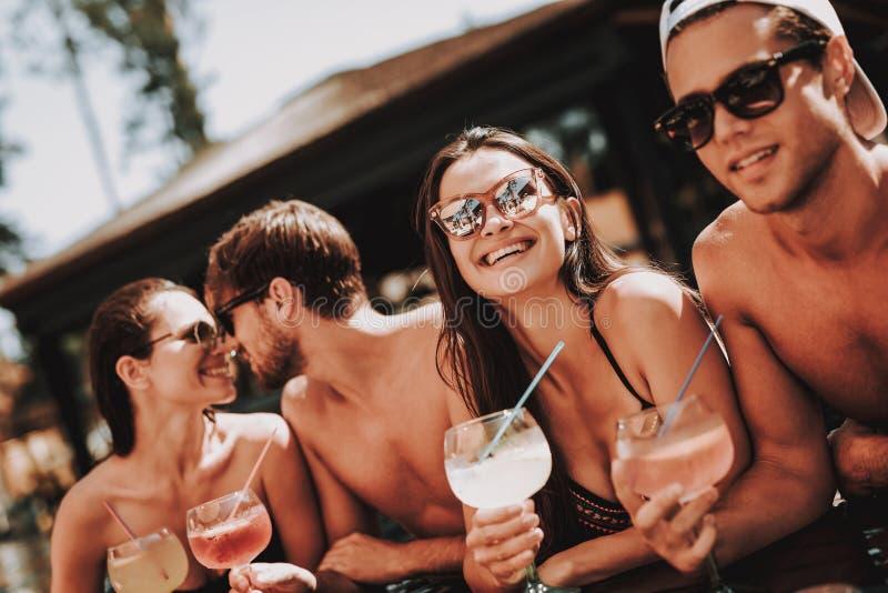 Junge lächelnde Freunde mit Cocktails am Poolside stockbilder