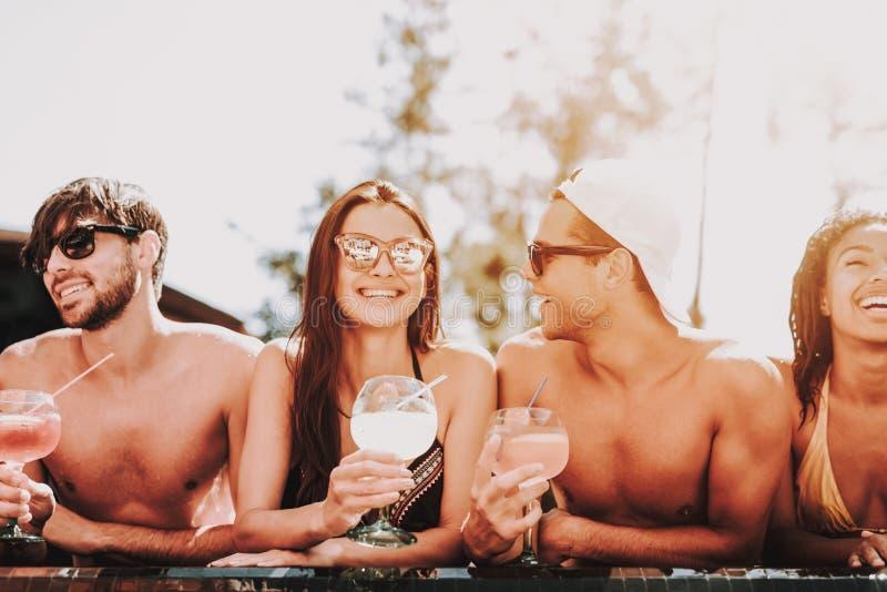 Junge lächelnde Freunde mit Cocktails am Poolside lizenzfreie stockbilder