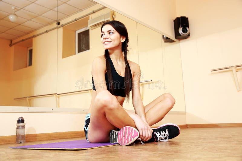 Junge lächelnde geeignete Frau, die auf Yogamatte sitzt stockfotos
