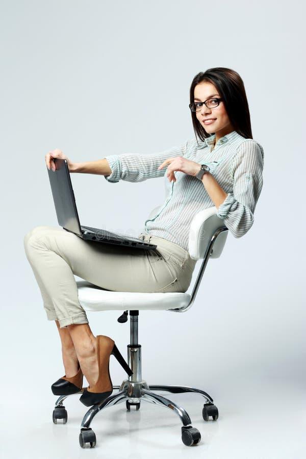 Junge lächelnde Geschäftsfrau, die auf dem Bürostuhl mit Laptop sitzt stockbilder