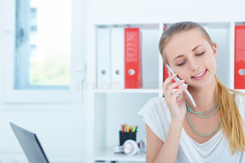 Junge lächelnde Geschäftsfrau, die am Telefon spricht und Anmerkungen in Büro schreibt lizenzfreies stockbild