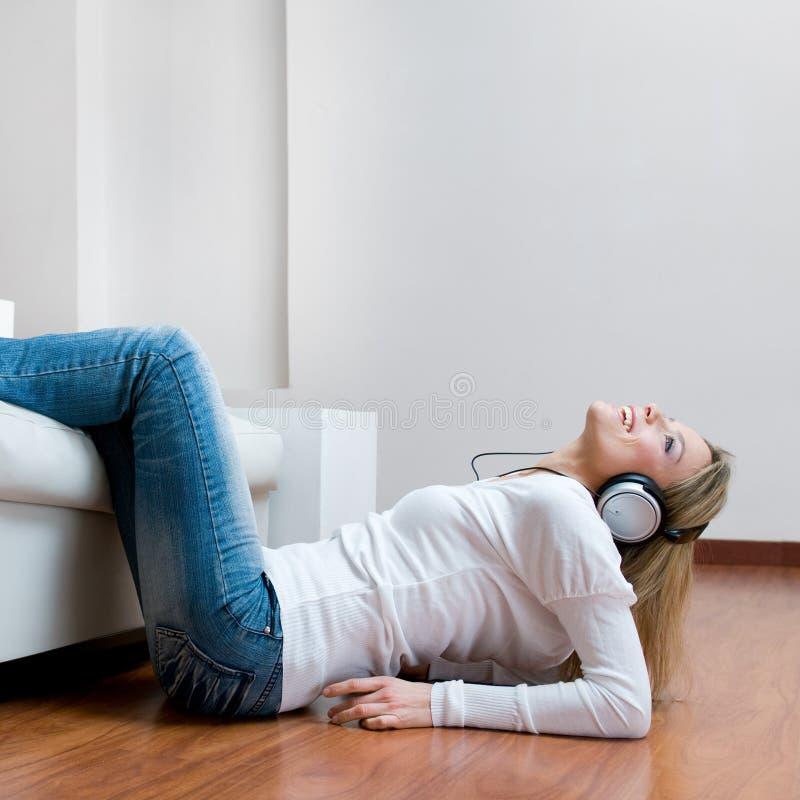Junge lächelnde hörende Musik der Frau lizenzfreies stockfoto