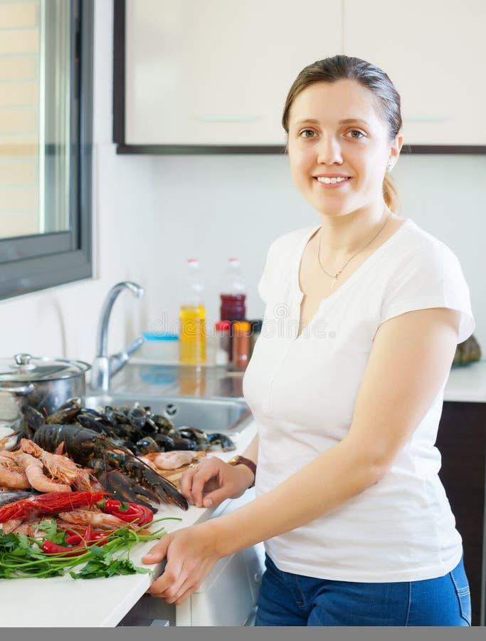 Junge lächelnde Hausfrau mit rohen Meeresfrüchten stockfotografie
