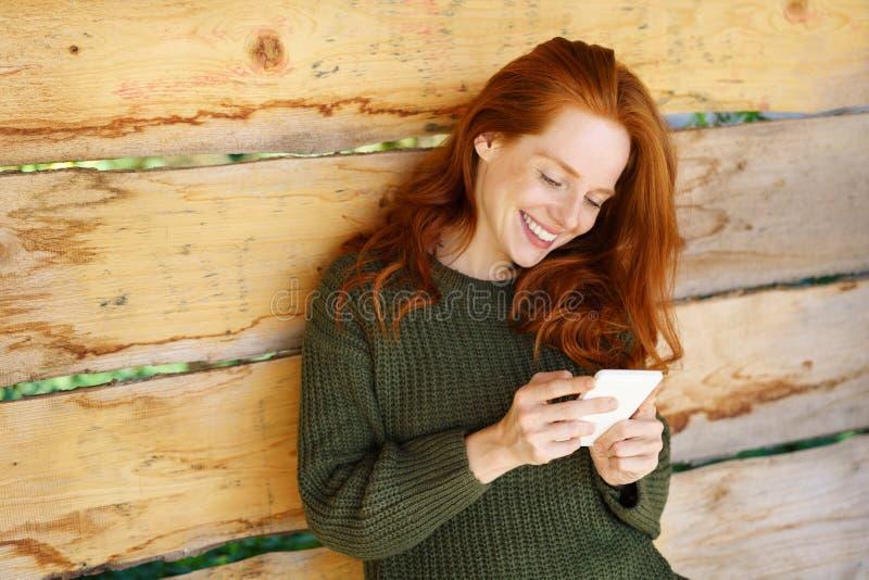 Junge lächelnde Ingwerfrau, die Telefon verwendet lizenzfreies stockbild