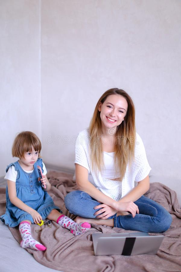 Junge lächelnde Mutter, die auf Bett mit kleiner Tochter nahe Laptop sitzt lizenzfreies stockfoto