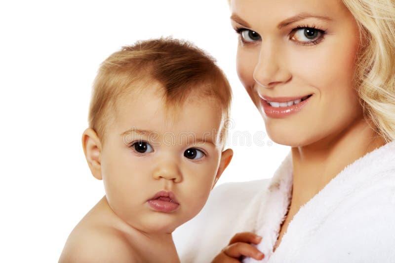 Junge lächelnde Mutter im Bademantel hält ihr Baby stockbild
