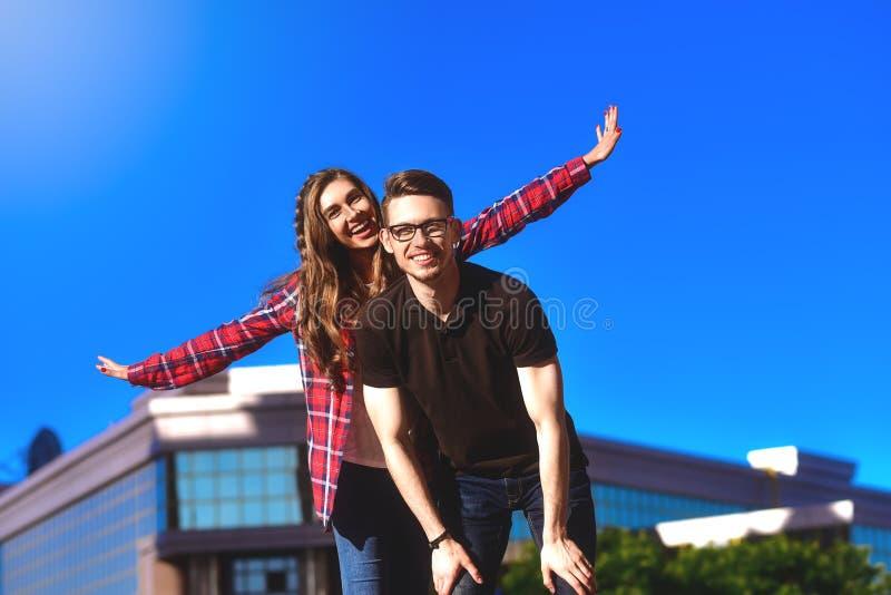 Junge lächelnde Paare, die Spaßdoppelpolreiten an der Straße haben stockbild