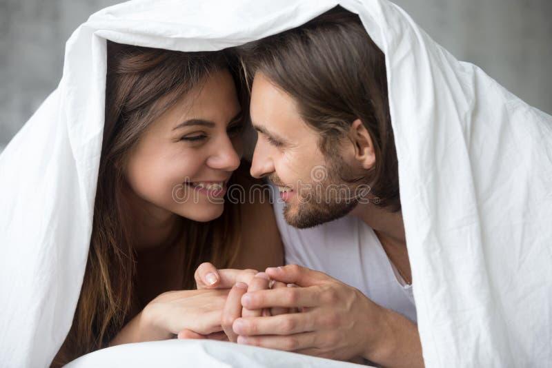 Junge lächelnde Paare im Bett, das den Spaß umfasst mit Decke hat stockfotos