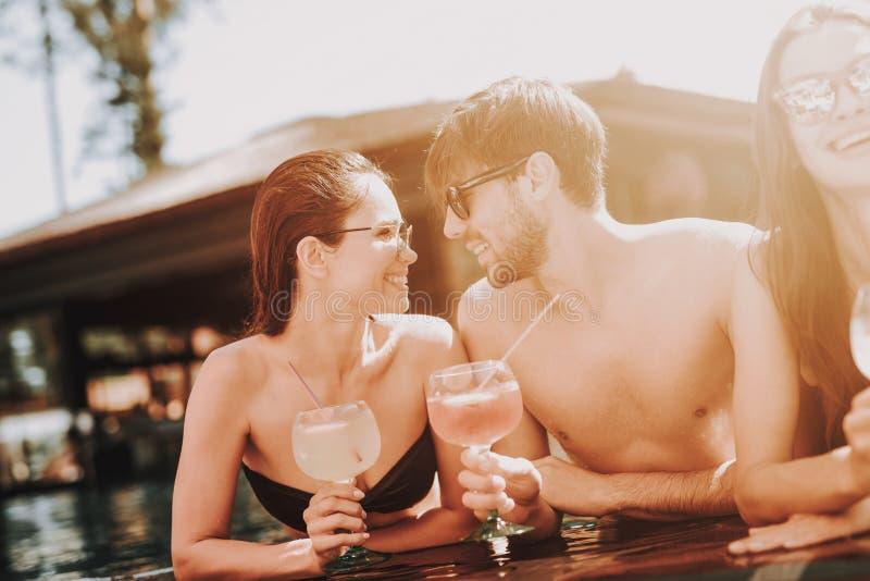 Junge lächelnde Paare mit Cocktails am Poolside lizenzfreie stockfotos