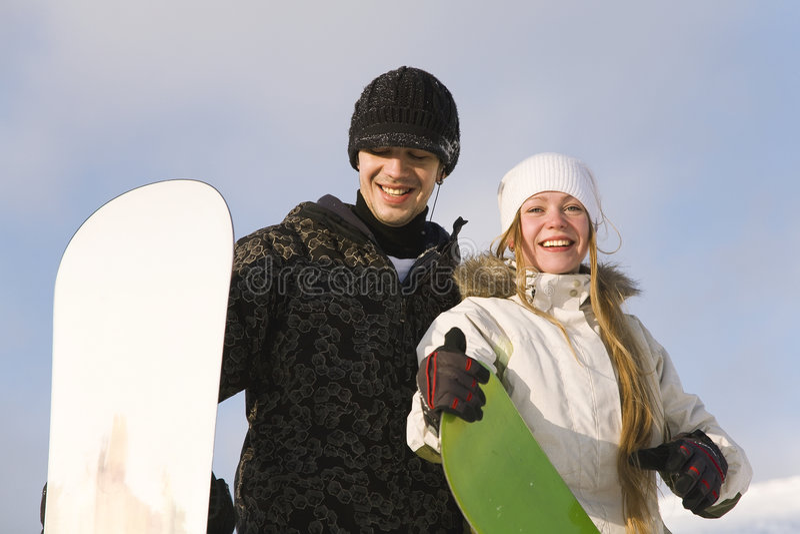 Junge lächelnde Paare mit Snowboards lizenzfreie stockfotos