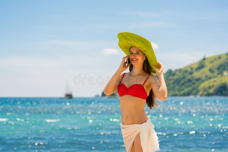 Junge lächelnde Schönheit bei der Unterhaltung am Handy auf dem Strand lizenzfreies stockbild