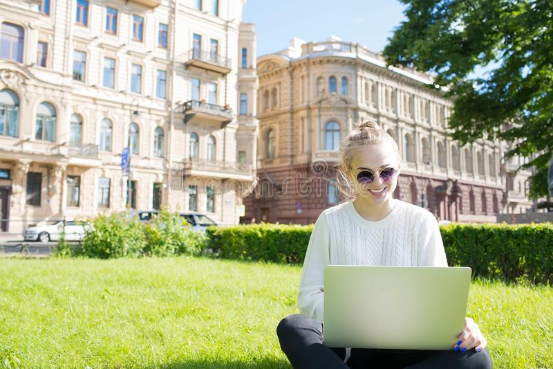 Junge lächelnde Studentin, die online über die Laptop-Computer, sitzend auf Universitätsgelände lernt stockfoto