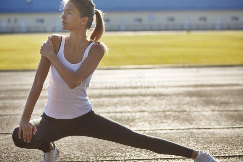 Junge Läufersitzfrau, die vor Übungen draußen streching ist Athletische weibliche Ausdehnung nach Training draußen Sport und stockfotos