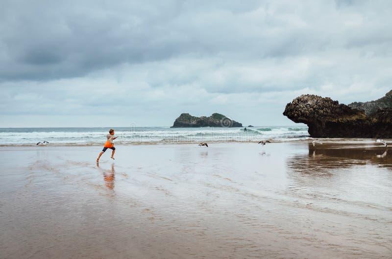 Junge läuft auf dem Ozeanstrand Regen nach lizenzfreie stockfotografie