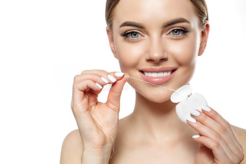 Junge lachende Frau mit großartigen schneeweißen Zähnen Mädchen mit einem gesunden Lächeln mit Bürste, Zahnpasta und Floß stockfotografie