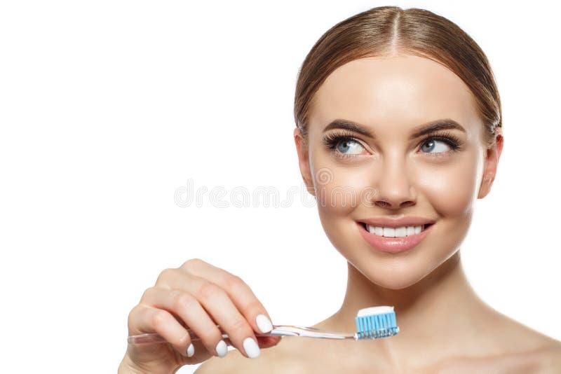 Junge lachende Frau mit großartigen schneeweißen Zähnen Mädchen mit einem gesunden Lächeln mit Bürste, Zahnpasta und Floß lizenzfreie stockfotos