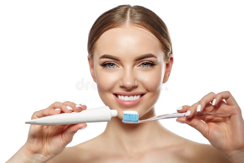 Junge lachende Frau mit großartigen schneeweißen Zähnen Mädchen mit einem gesunden Lächeln mit Bürste, Zahnpasta und Floß stockfoto