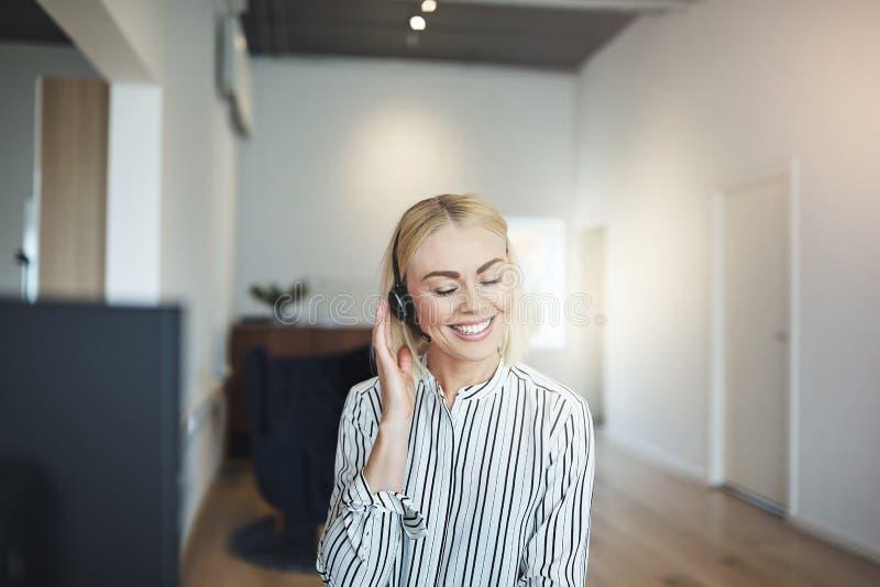 Junge lachende Geschäftsfrau bei der Unterhaltung auf einem Kopfhörer bei der Arbeit lizenzfreies stockbild