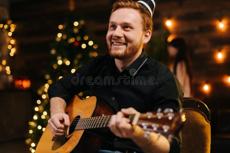 Junge Lacher spielen Gitarre Guy sieht glücklich und sorglos aus stockfoto