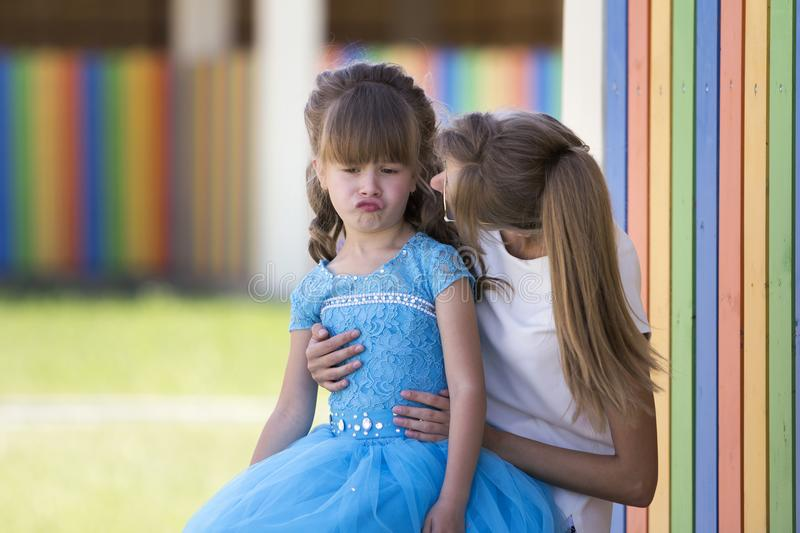 Junge langhaarige Mutter oder Schwester, die an ihre Knie halten und recht kleines schwermütiges unzufriedenes Mädchen im blauen  stockfotos
