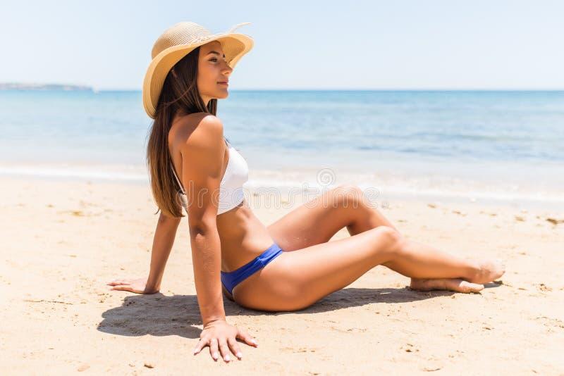 Junge lateinische Frau im Strohhut, der auf tropischem Strand liegt lizenzfreie stockfotografie